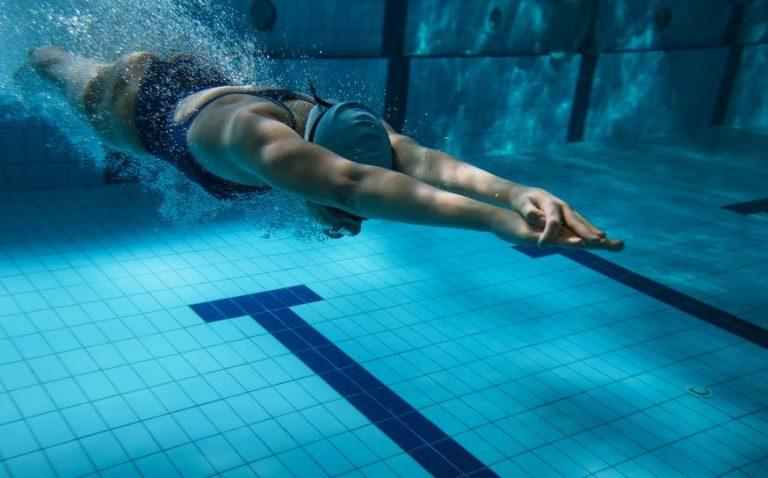 Frau taucht nach Startsprung ins Wasser ein