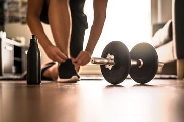 Mann bindet sich die Schuhe, um dann zuhause zu trainieren