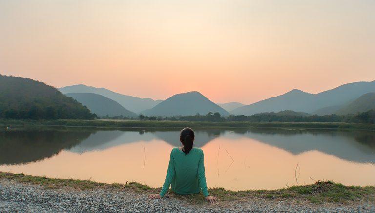 Frau entspannt an einem ruhigen See bei Sonnenuntergang