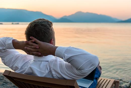Mann liegt auf einer Liege am See und entspannt