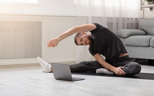 Mann dehnt sich auf dem Boden seines Wohnzimmers vor den Laptop