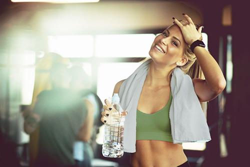 Frau im Fitnessstudio mit Wasserflasche in der Hand