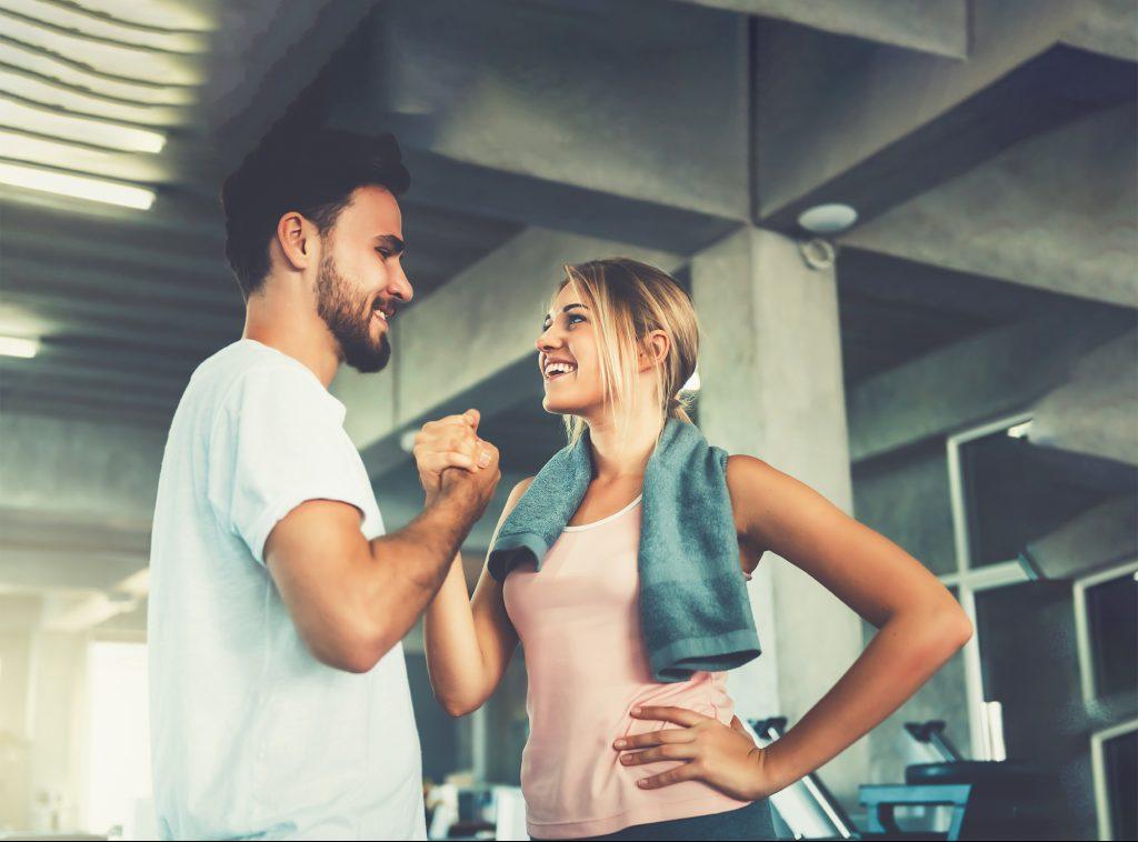 Mann und Frau schlagen im Fitnessstudio ein und zeigen Motivation