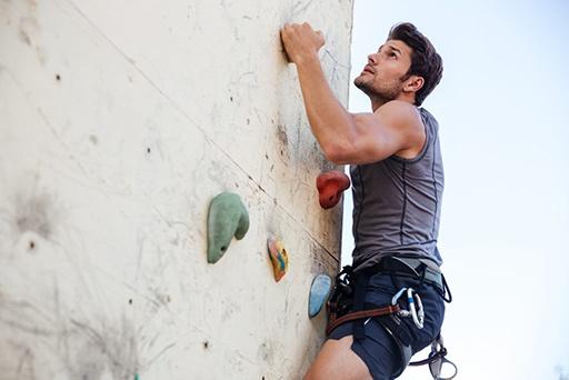 Mann mit Kletterausrüstung klettert eine Übungswand hoch