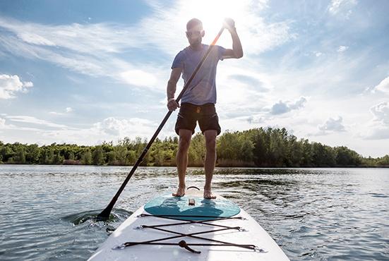 Mann beim Stand up Paddling im See