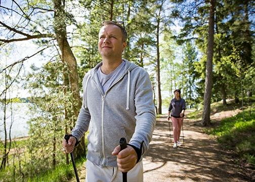 Mann und Frau machen Nordic Walking im Wald