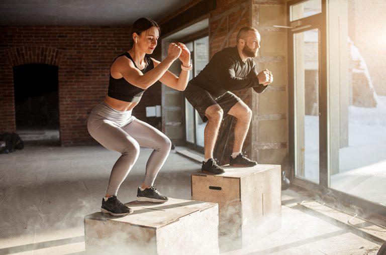 Mann und Frau springen auf Plyoboxen