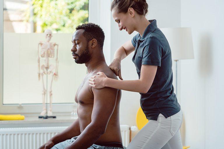 Physiotherapeutin behandelt Mann am Schulterblatt