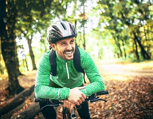 Radfahrer lehnt sich über seinen Fahrradlenker
