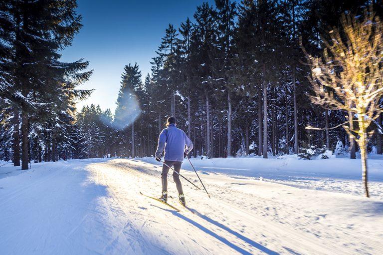 Mann skatet auf Langlaufskiern durch den verschneiten Wald