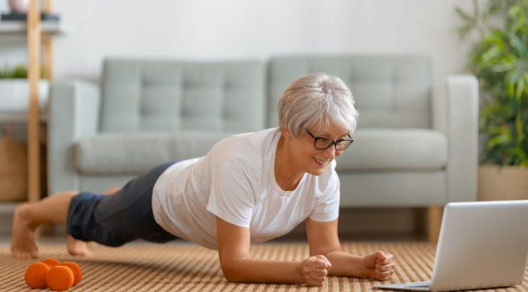 Ältere Frau macht eine Plank Zuhause vor dem Laptop