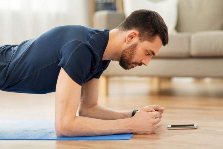 Mann macht Plank zuhause und schaut dabei auf sein Handy