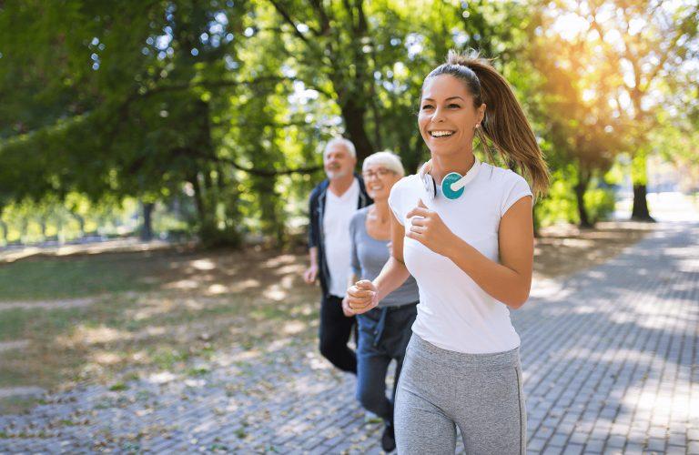 Frau geht gemeinsam mit zwei älteren Personen im Park laufen